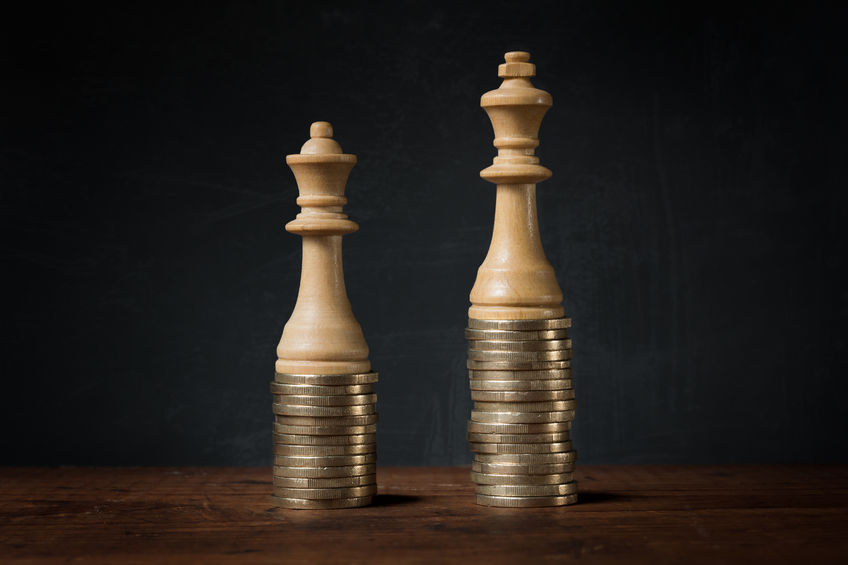 Two Chess pieces standing on two stacks of 20p. Queen Chess piece lower than King Chess piece representing Gender Pay Gap.