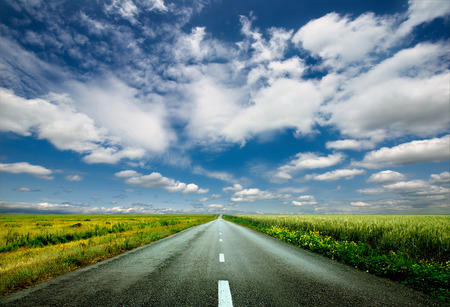 a blue sky with clouds, with a long straight road with grass either side