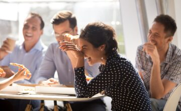 Office staff laughing together at lunchtime Image Source