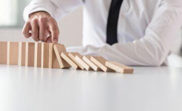 Businessperson stopping toppling line of blocks