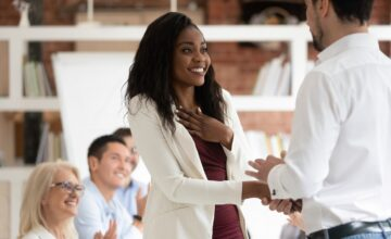 Woman receiving employee recognition in meeting
