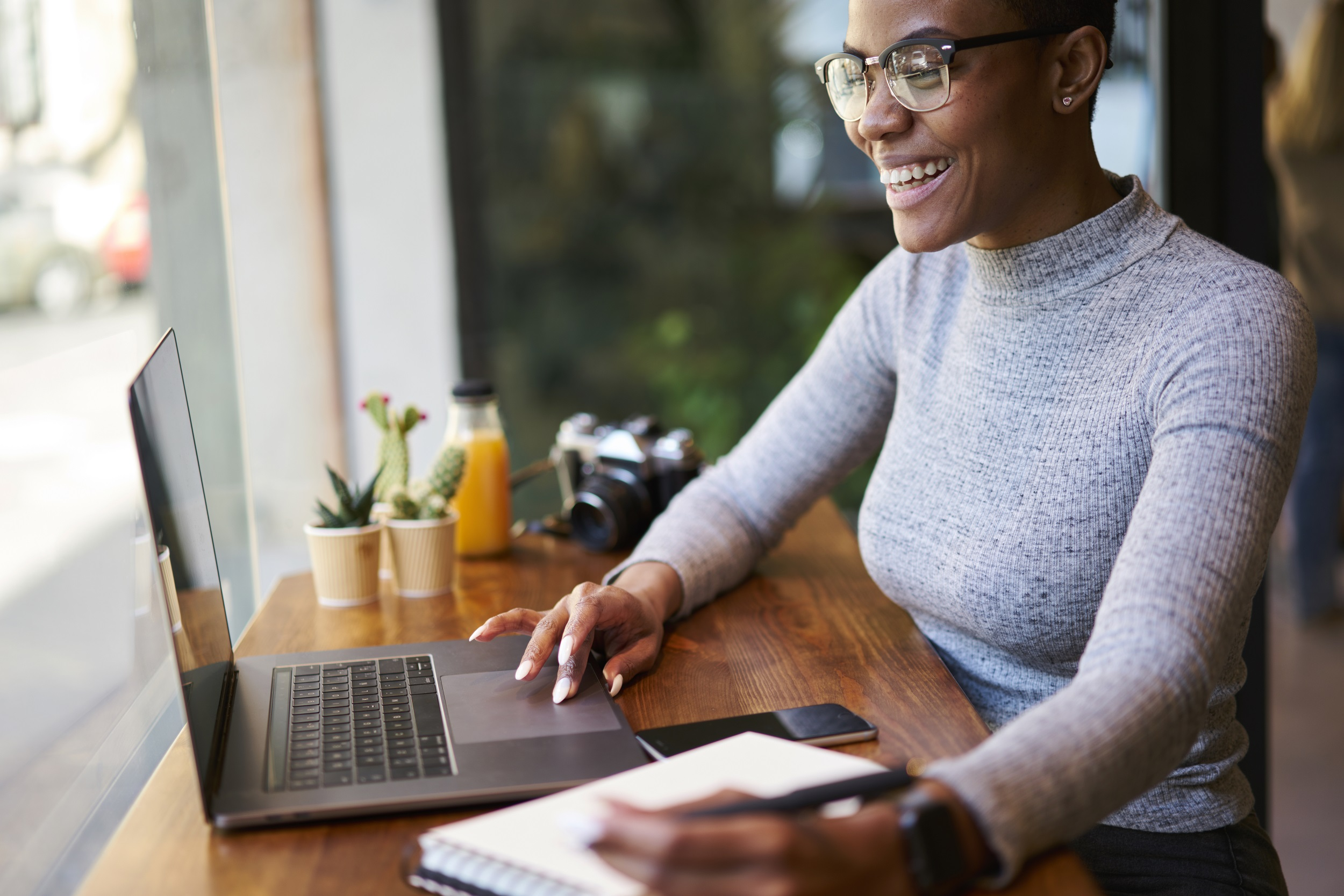 Businesswoman smiling at laptop screen whilst working remotely
