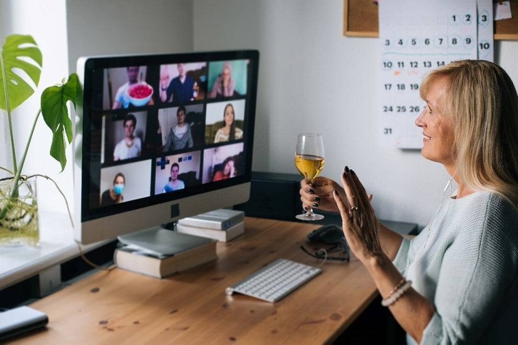 Woman taking part in virtual happy hour with wine
