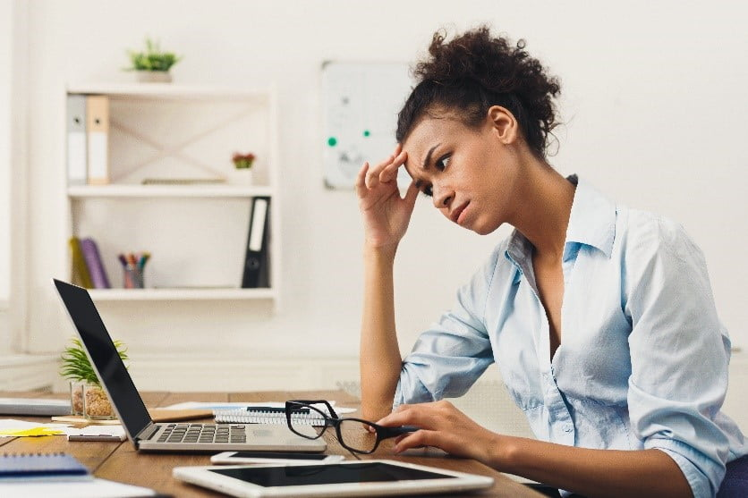 stressed office worker looking at laptop